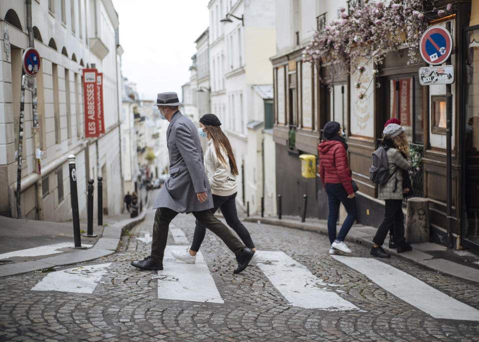 People wearing face masks walk, in the Montmartre district of Paris, Sunday Oct. 25, 2020. A curfew intended to curb the spiraling spread of the coronavirus, has been imposed in many regions of France including Paris and its suburbs. (AP Photo/Lewis Joly)