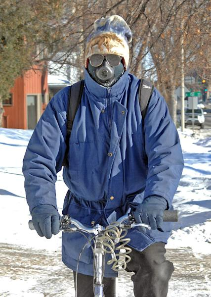 Jon Kramer, of Bismarck said a good way to beat the cold conditions is with a face mask called the cold avenger. Kramer uses the unusual looking face mask to break the wind as he rides his bicycle Monday Jan. 6, 2014. (AP Photo/The Tribune, Tom Stromme)
