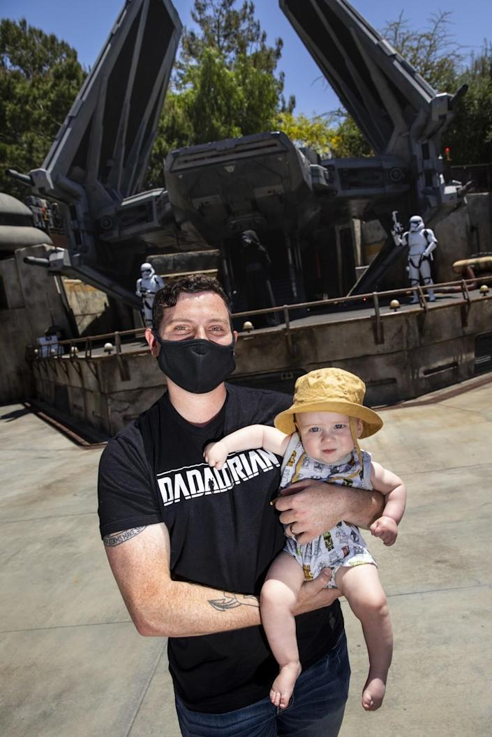 """A man in a """"Dadalorian"""" shirt holds a baby in a Star Wars onesie."""