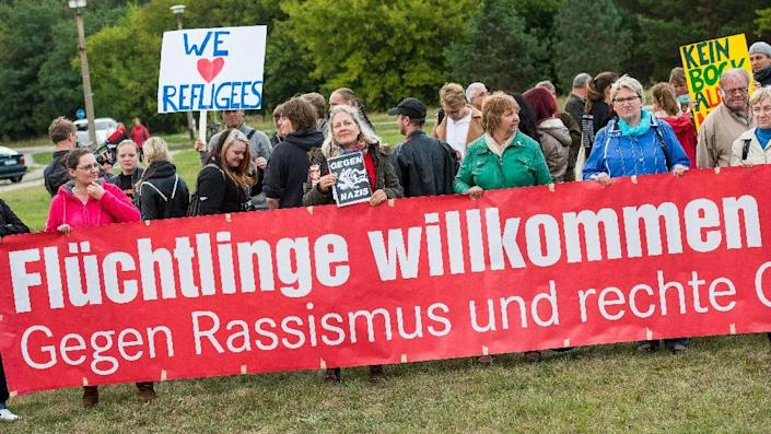 """People hold up a banner which reads """"Refugees welcome - Against rasicm"""" during a rally at the registry center for refugees in Eisenhuettenstadt, Germany on September 9, 2015 (AFP Photo/Patrick Pleul)"""