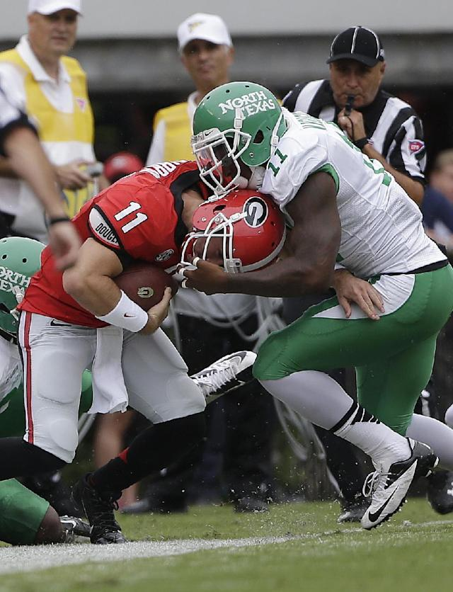 Georgia quarterback Aaron Murray (11) is wrestled out-of-bounds by North Texas linebacker Will Wright (11) in the first half of an NCAA college football game Saturday, Sept. 21, 2013 in Athens, Ga. (AP Photo/John Bazemore)