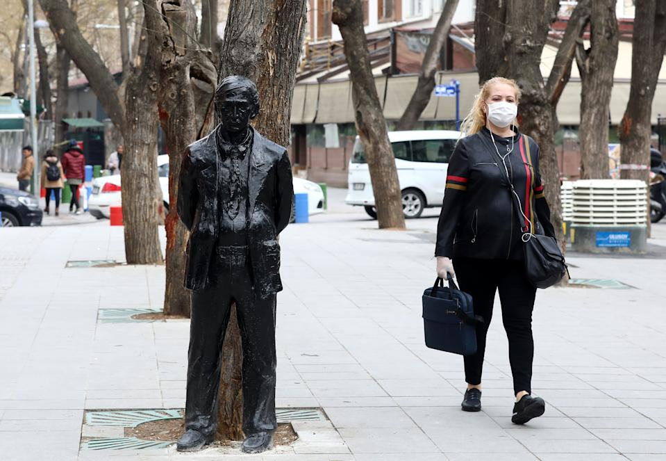 A pedestrian wearing a facemask walks past a statue on a pavement in Ankara on March 30, 2020, as authorities urged residents to stay at home as part of coronavirus (COVID-19) precautions. - Turkey has confirmed some 105 deaths and 9217 positive cases of the new coronavirus (COVID-19). (Photo by Adem ALTAN / AFP) (Photo by ADEM ALTAN/AFP via Getty Images)