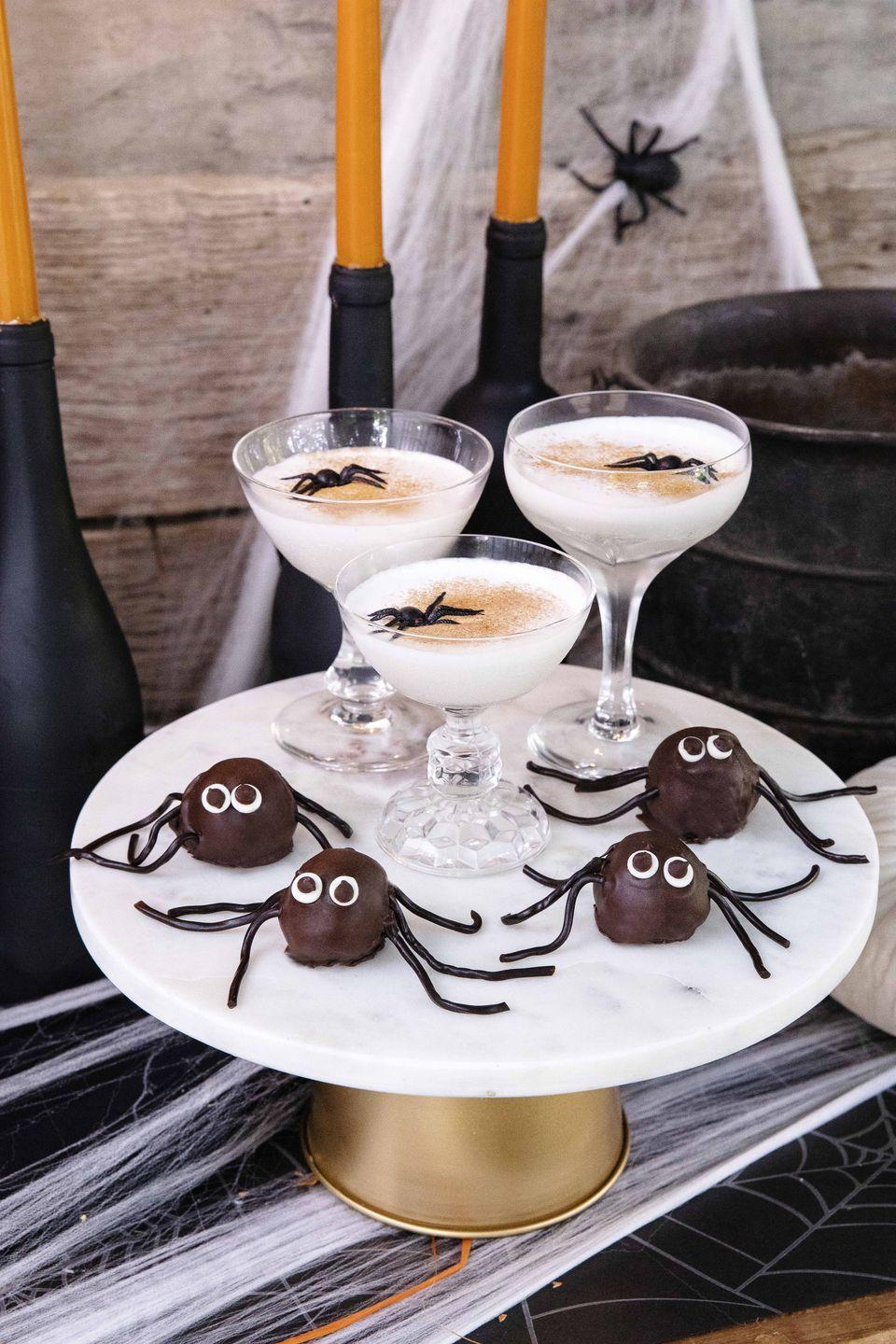 """<p>Garnished with pumpkin spice and a creepy spider, this take on a White Russian is just the thing for a grown-up holiday bash.</p><p><strong><a href=""""https://www.countryliving.com/food-drinks/a33943308/liquid-web-cocktails/"""" rel=""""nofollow noopener"""" target=""""_blank"""" data-ylk=""""slk:Get the recipe"""" class=""""link rapid-noclick-resp"""">Get the recipe</a>.</strong></p>"""