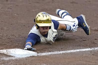 Notre Dame's Brooks Coetzee (42) reaches back to tag first base after the ball gets away from Mississippi State's first baseman during an NCAA college baseball super regional game, Sunday, June 13, 2021, in Starkville, Miss. (AP Photo/Rogelio V. Solis)