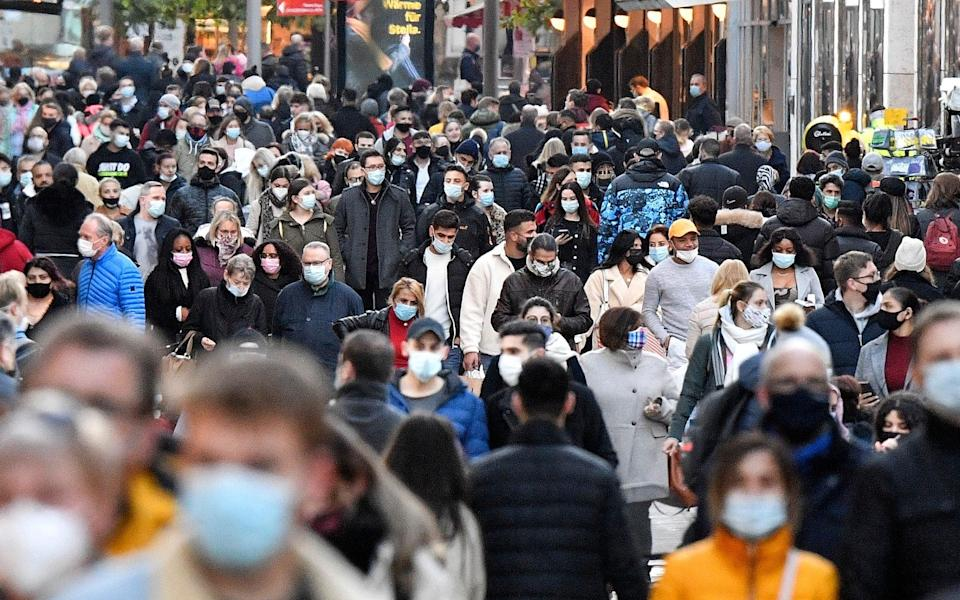 People wearing mandatory face masks in a shopping street in Dortmund, Germany - Martin Meissner/AP