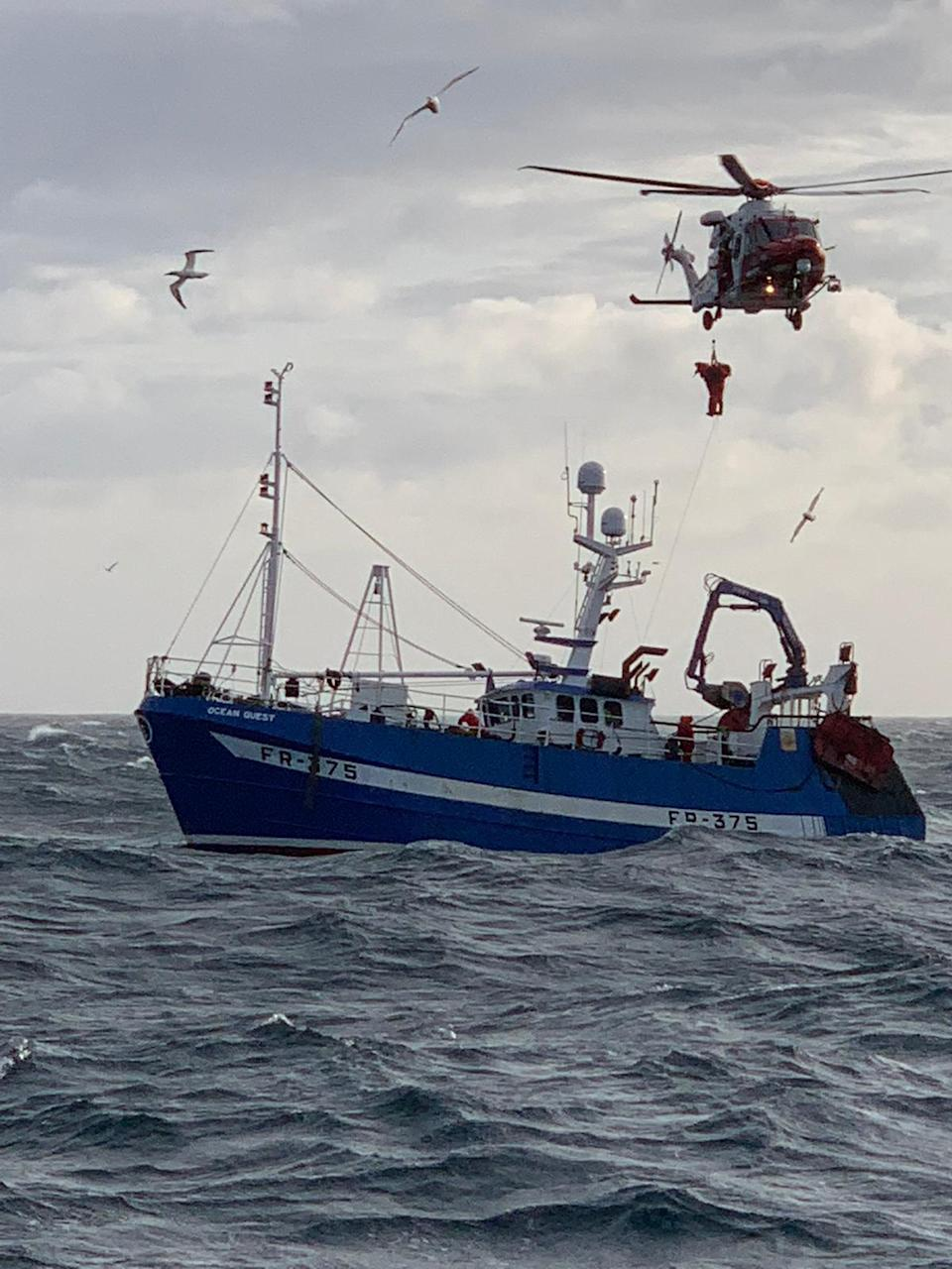 Crew being winched up to the rescue helicopter