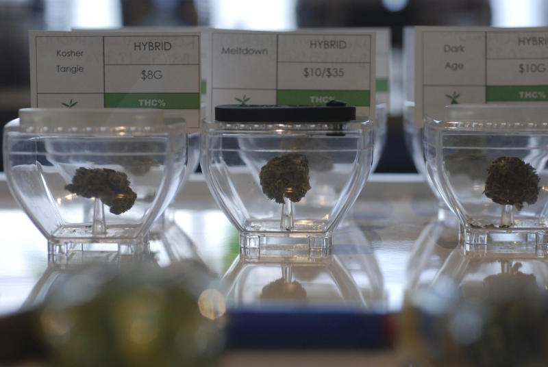 FILE - In this June 11, 2019 file photo Medical marijuana flowers await customers at the Minerva cannabis dispensary in Santa Fe, N.M. New Mexico would legalize recreational marijuana sales without exceptions for dissenting cities and counties under a rebooted proposal form legislators that emphasizes small business opportunities and ready access to pot for 80,000 current medical cannabis patients. Legalization for the first time enjoys the full throttled support of second-year Democratic Gov. Michelle Lujan Grisham, who set up a volunteer commission last year to vet health and public safety concerns about recreational cannabis and on Thursday, Jan. 16, 2020, pitched the benefits of the pot economy to a gathering business leaders. (AP Photo/Morgan Lee,File)