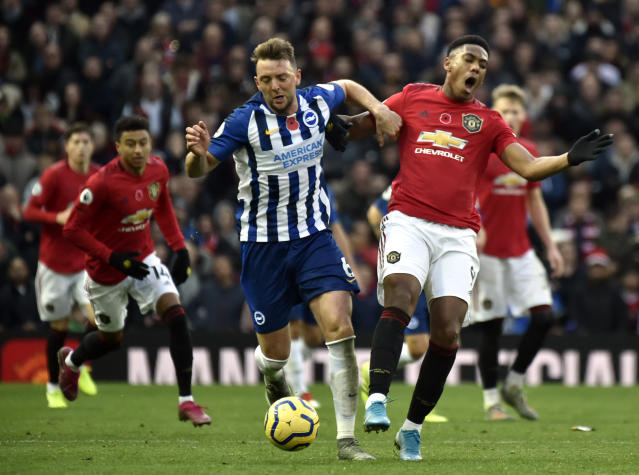 Brighton's Dale Stephens, center, duels for the ball with Manchester United's Anthony Martial during the English Premier League soccer match between Manchester United and Brighton and Hove Albion, at the Old Trafford stadium in Manchester, England, , Sunday, Nov. 10, 2019. (AP Photo/Rui Vieira)