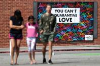 People walk in front of a mural, as the global outbreak of the coronavirus disease (COVID-19) continues, in Santa Monica