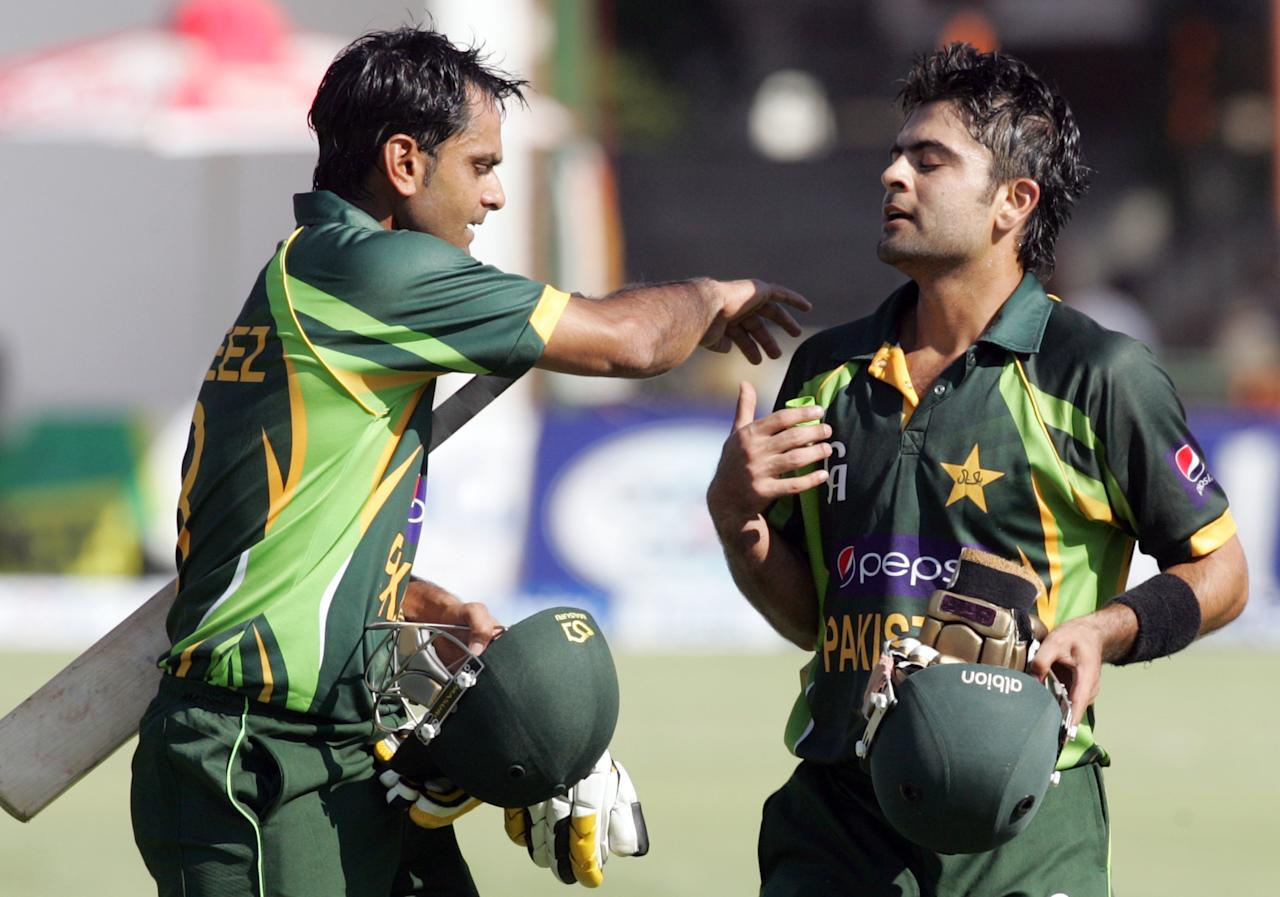 Pakistan's captain Muhammad Hafeez (L) congratulates team mate Ahmed Shehzad (R) on reaching 98 runs during the second and final Twenty20 international between Zimbabwe and Pakistan at the Harare Sports Club on August 24, 2013.   AFP PHOTO / JEKESAI NJIKIZANA        (Photo credit should read JEKESAI NJIKIZANA/AFP/Getty Images)