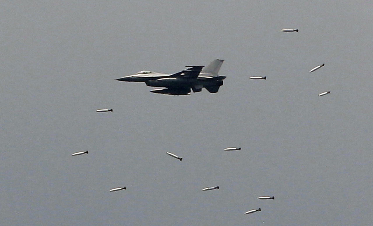 In this photo taken Tuesday, June 19, 2012, a South Korean Air Forces' KF-16 fighter drops bombs during a South Korea-U.S. joint military live-fire drills at Seungjin Fire Training Field in Pocheon, South Korea, near the border with the North Korea. The drills were held in a show of combat readiness ahead of the 62nd anniversary of the start of the Korean War on June 25. (AP Photo/Lee Jin-man)