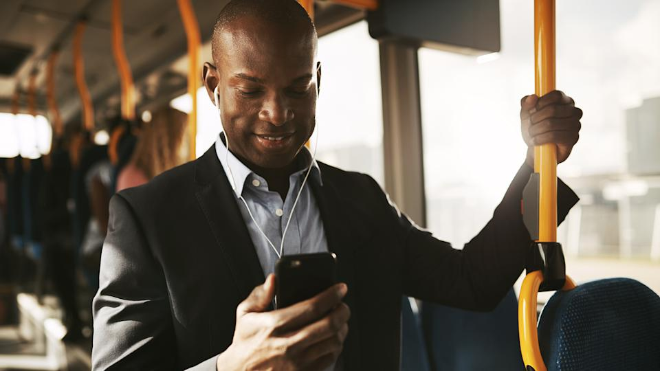 Smiling young African businessman wearing a suit standing on a bus during his morning commute listening to music on a smartphone and earphones.