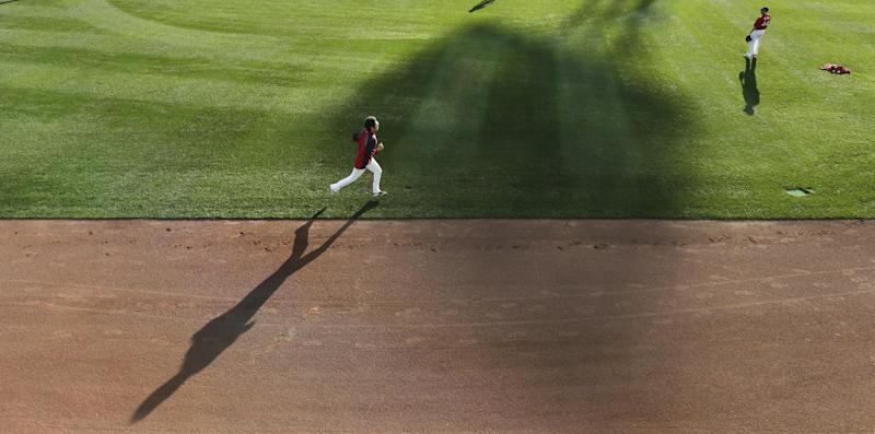 Boston Red Sox relief pitcher Koji Uehara runs next to the warning track during practice at Fenway Park, Friday, Oct. 18, 2013, in Boston. The Red Sox will face the Detroit Tigers in Game 6 of the American League baseball championship series on Saturday. (AP Photo/Charles Krupa)
