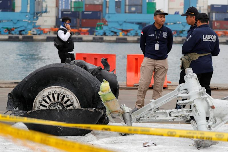 Forensic officers stand by a damaged tyre from last month's fatal Lion Air crash. On Wednesday, another Lion Air plane was involved in an incident on an airport runway: Reuters