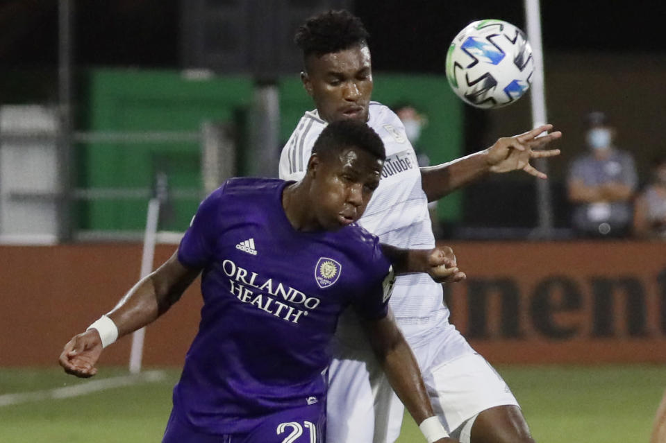 Orlando City midfielder Andres Perea (21) hits the ball as Los Angeles FC midfielder Jose Cifuentes (11) closes in during the second half of an MLS soccer match, Friday, July 31, 2020, in Orlando, Fla. (AP Photo/John Raoux)
