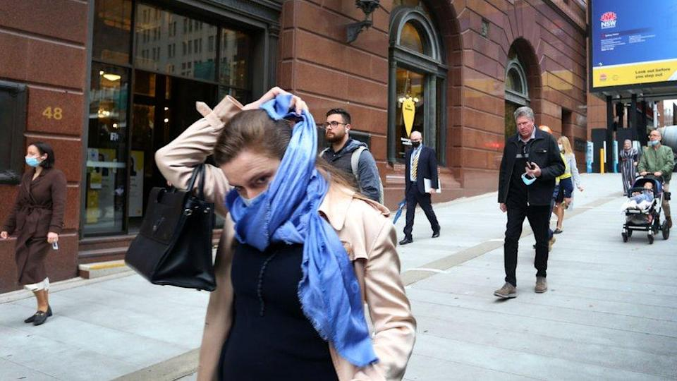 A woman walking through Sydney's city centre wraps a scarf around her face
