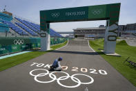 A worker paints Olympic rings at the finish line of the BMX racing track as preparations continue for the 2020 Summer Olympics, Tuesday, July 20, 2021, at the Ariake Urban Sports Park in Tokyo. (AP Photo/Charlie Riedel)
