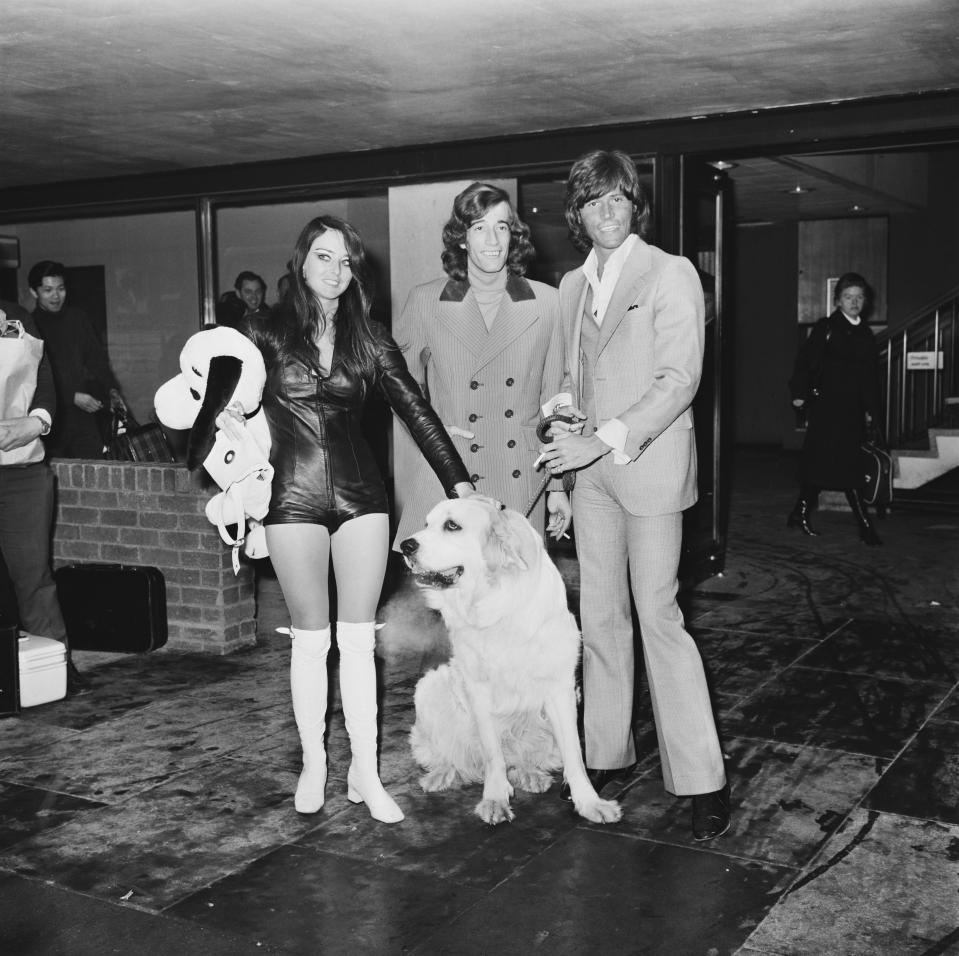 Singers Barry (right) and Robin Gibb (1949 - 2012) of the Bee Gees return from the US with Barry's wife, former Miss Edinburgh Linda Gray, London Airport, UK, 8th March 1971. (Photo by George Stroud/Daily Express/Getty Images)