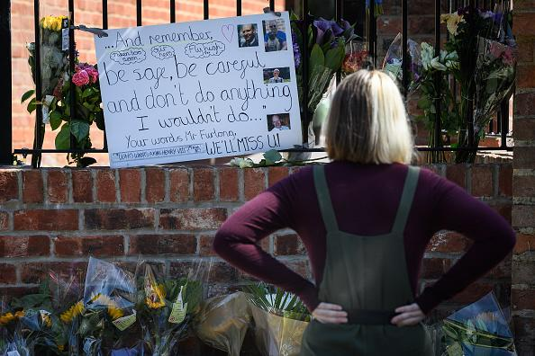 Students and parents lay flowers and pay their respects to the murdered school teacher James Furlong outside The Holt School in Wokingham, England.