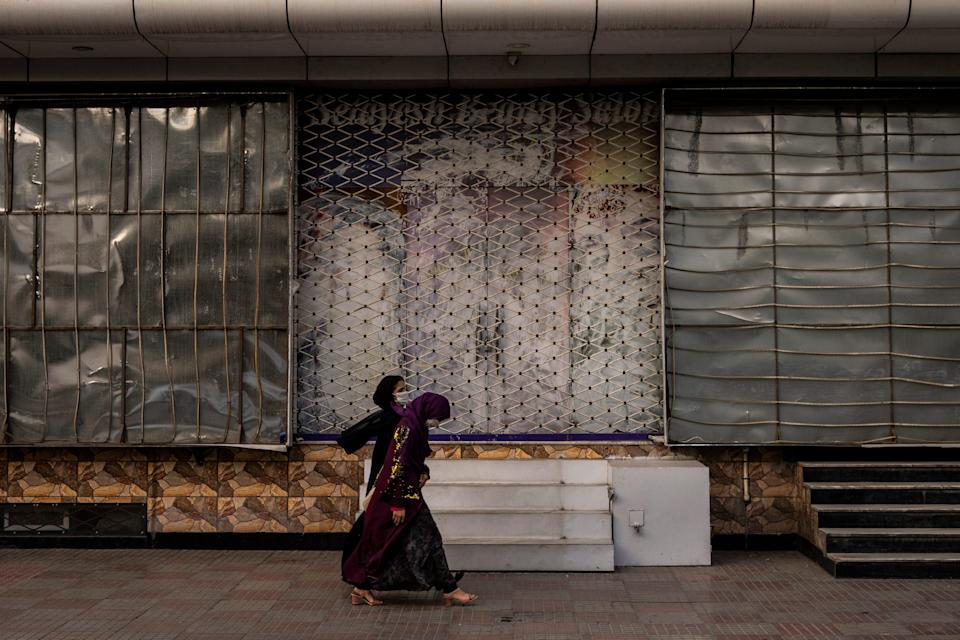 Afghan women walk past a closed beauty salon in Kabul, Afghanistan, Saturday, Sept. 11, 2021. Since the Taliban gained control of Kabul, several images depicting women outside beauty salons have been removed or covered up.