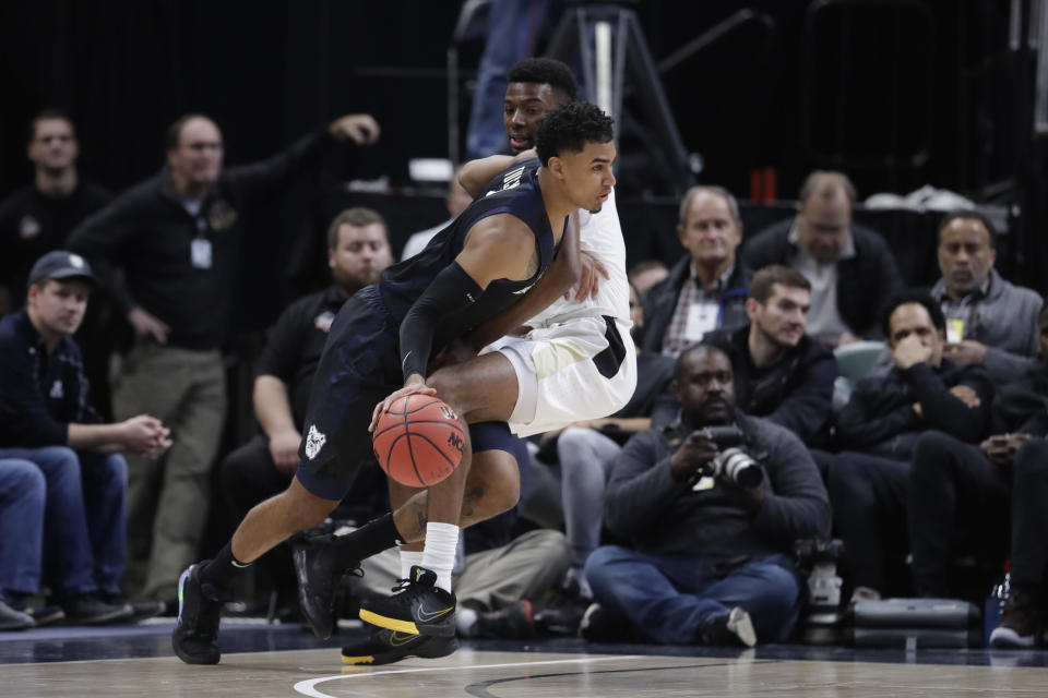 Butler's Jordan Tucker (1) is fouled by Purdue's Aaron Wheeler (1) during the first half of an NCAA college basketball game, Saturday, Dec. 21, 2019 in Indianapolis. (AP Photo/Darron Cummings)