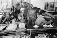 <p>Kids wait on long lines to grab their lunch from the cafeteria. </p>