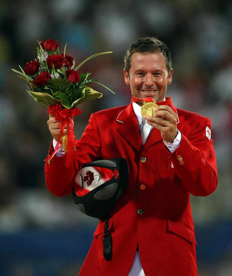 HONG KONG, CHINA - AUGUST 21: Eric Lamaze of Canada poses with the gold medal after he and his horse Hickstead won the Individual Jumping held at the Hong Kong Olympic Equestrian Venue in Sha Tin during day 13 of the Beijing 2008 Olympic Games on August 21, 2008 in Hong Kong, China. (Photo by Julian Herbert/Getty Images)