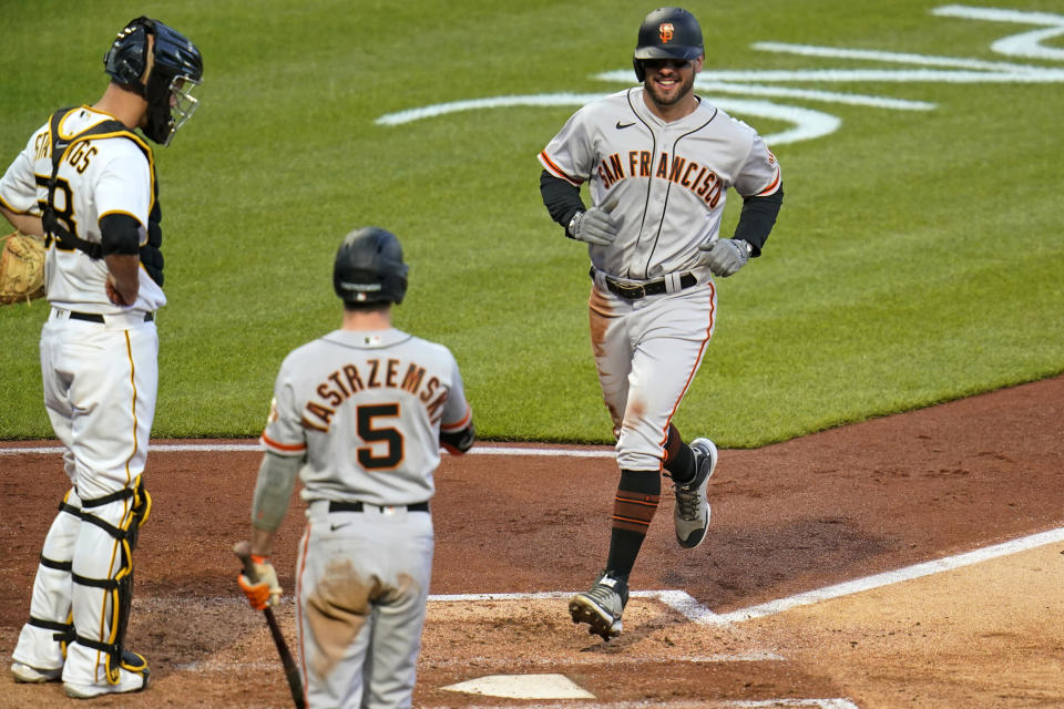 San Francisco Giants' Mike Tauchman, right, scores on an errant pickoff throw to third base by Pittsburgh Pirates catcher Jacob Stallings, left, during the fifth inning of a baseball game in Pittsburgh, Thursday, May 13, 2021.(AP Photo/Gene J. Puskar)