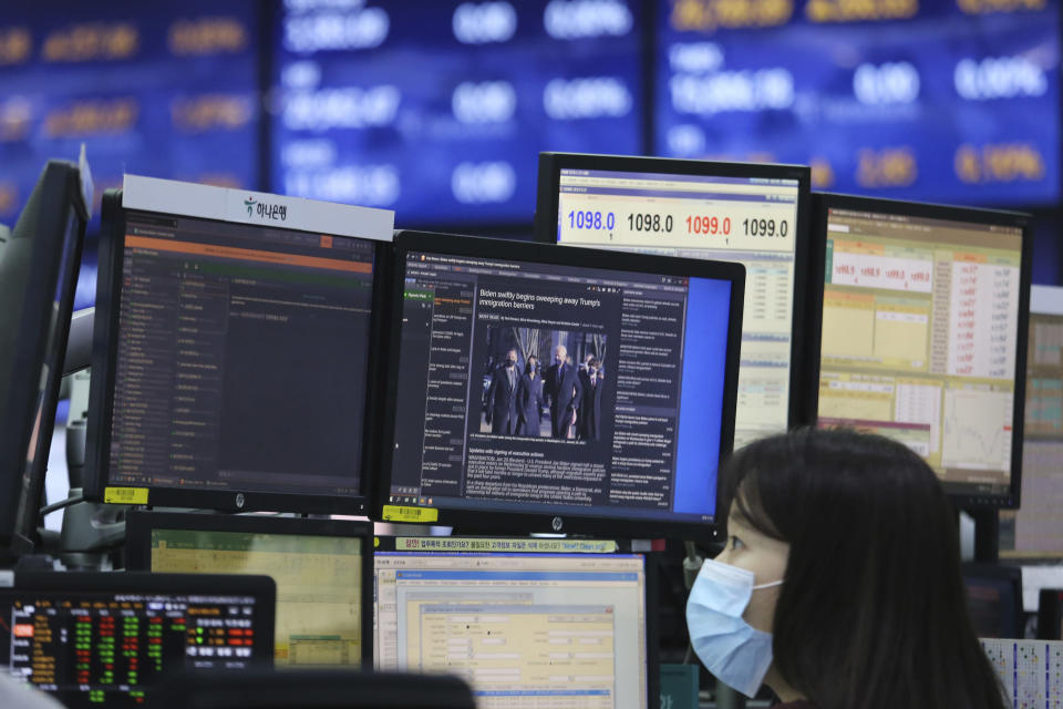 A screen shows a news report about U.S. President Joe Biden's inauguration as a currency trader works at the foreign exchange dealing room of the KEB Hana Bank headquarters in Seoul, South Korea, Thursday, Jan. 21, 2021. (AP Photo/Ahn Young-joon)