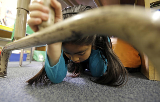 """FILE - In this Oct. 17, 2013 file photo, Lillian Zurita shows the proper way to """"drop, cover and hold on"""" in Ms. Irvin's second-grade class during an earthquake drill known as the Great Shakeout at Rosemont Elementary School near downtown Los Angeles. Twenty-five years ago this week, on Jan. 17, 1994, a violent, pre-dawn earthquake shook Los Angeles from its sleep, and sunrise revealed widespread devastation, with dozens killed and $25 billion in damage. (AP Photo/Reed Saxon, File)"""