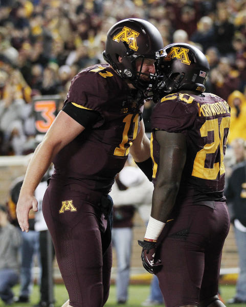 Minnesota quarterback Max Shortell, left, and running back Donnell Kirkwood celebrate Kirkwood's rushing touchdown in the second half of an NCAA college football game against Syracuse in Minneapolis on Saturday, Sept. 22, 2012. Minnesota defeated Syracuse 17-10. (AP Photo/Andy King)