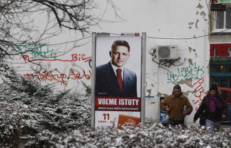 Residents walk past an election poster with the chairman of the SMER-Social Democracy party Robert Fico in Bratislava, Slovakia, Thursday, March 8, 2012. Slovakia is holding early general elections on Saturday, March 10, 2012. (AP Photo/Petr David Josek)