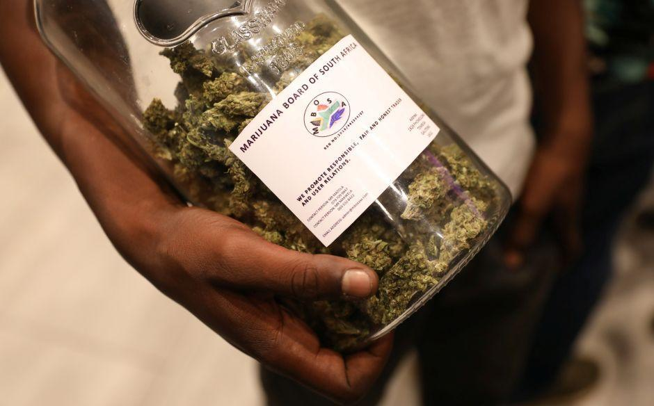A man holds a jar full of cannabis buds at a 2018 expo in South Africa.