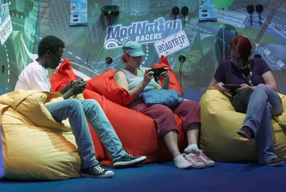 Visitors play Playstations at an exhibition stand during the Gamescom 2012 fair in Cologne August 15, 2012.