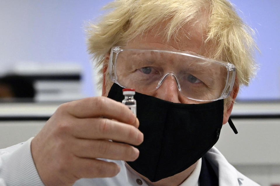 Britain's Prime Minister Boris Johnson holds a vial of the Oxford/AstraZeneca vaccine Covid-19 candidate vaccine, known as AZD1222, at Wockhardt's pharmaceutical manufacturing facility in Wrexham, Wales, Monday, Nov. 30, 2020. (Paul Ellis/PA via AP)