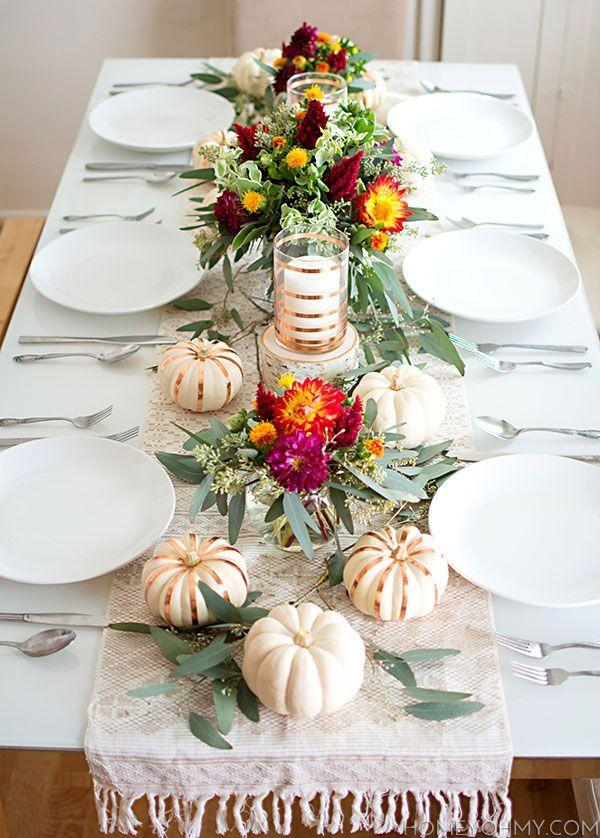 """<p>Stripes of copper tape adorn both the mini pumpkins and candle holders along blogger Amy's Thanksgiving table, while blooms from Trader Joe's provide bright pops of color. </p><p><strong><strong>Get the tutorial</strong> at </strong><strong><a href=""""http://www.homeyohmy.com/fall-tablescape/"""" rel=""""nofollow noopener"""" target=""""_blank"""" data-ylk=""""slk:Homey Oh My!"""" class=""""link rapid-noclick-resp"""">Homey Oh My!</a></strong></p><p><strong><a class=""""link rapid-noclick-resp"""" href=""""https://www.amazon.com/Elanze-Designs-Decorative-Pumpkins-Quantity/dp/B07CHVVC1S?tag=syn-yahoo-20&ascsubtag=%5Bartid%7C10050.g.2130%5Bsrc%7Cyahoo-us"""" rel=""""nofollow noopener"""" target=""""_blank"""" data-ylk=""""slk:SHOP FAUX WHITE PUMPKINS"""">SHOP FAUX WHITE PUMPKINS</a></strong></p>"""