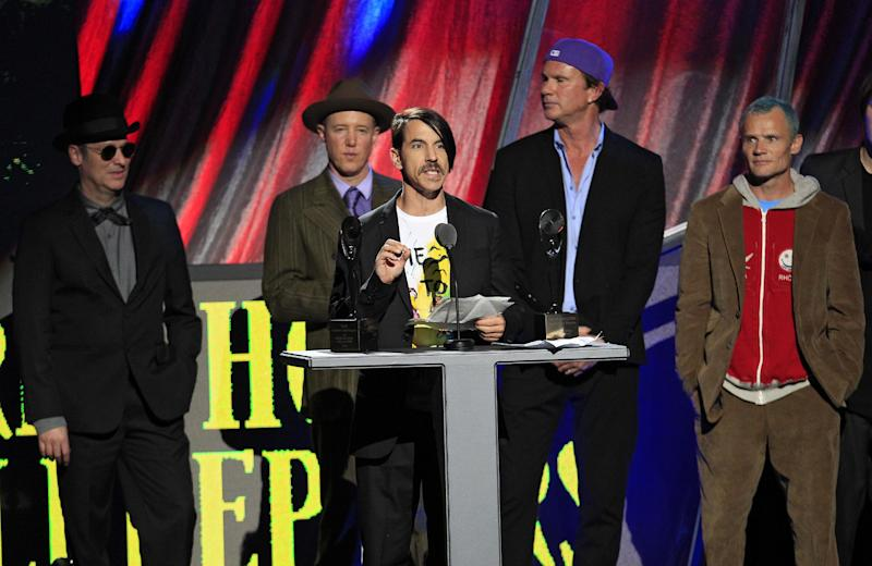 """Red Hot Chili Peppers' Anthony Kiedis speaks after induction into the Rock and Roll Hall of Fame Sunday, April 15, 2012, in Cleveland. Former members Cliff Martinez, far left, and Jack Irons, join Chad Smith, second from right, and Mike """"Flea"""" Balazary, right, onstage. (AP Photo/Tony Dejak)"""