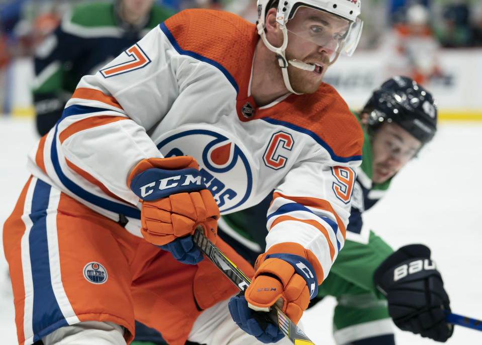 Edmonton Oilers centre Connor McDavid (97) fights for control of the puck with Vancouver Canucks defenseman Quinn Hughes (43) during the first period of an NHL hockey game Thursday, Feb. 25, 2021, in Vancouver, British Columbia. (Jonathan Hayward/The Canadian Press via AP)