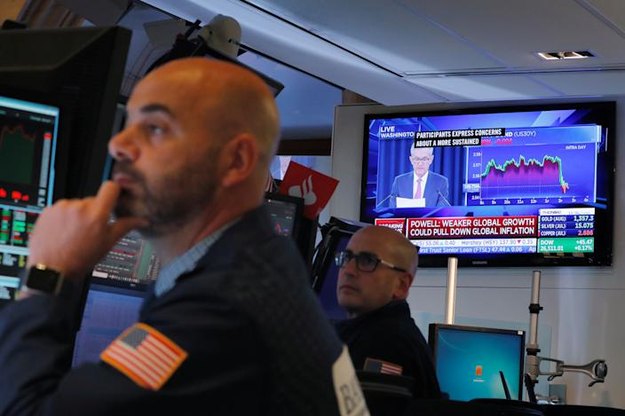 Traders work on the floor of the New York Stock Exchange as Federal Reserve Chairman Jerome Powell holds a news conference on the television behind them in New York, U.S., June 19, 2019.  REUTERS/Lucas Jackson