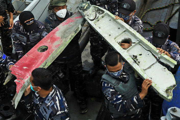 Indonesia navy sailors carry debris recovered from the waters off Java Island where a Sriwijaya Air passenger jet crashed on Saturday near Jakarta, Indonesia, Sunday, Jan. 10, 2021. Indonesian divers on Sunday located parts of the wreckage of the Boeing 737-500 at a depth of 23 meters (75 feet) in the Java Sea, a day after the aircraft with dozens of people onboard crashed shortly after takeoff from Jakarta. (AP Photo/Azwar Ipank)