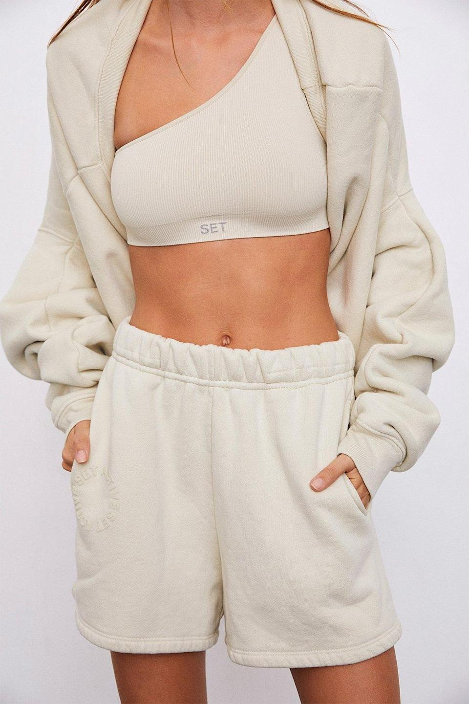 """Set Active's bestselling cream shorts are a prime pick for a post-workout brunch date. Take cues from the styling and throw slouchy <a href=""""https://www.glamour.com/gallery/best-bolero-sweaters?mbid=synd_yahoo_rss"""" rel=""""nofollow noopener"""" target=""""_blank"""" data-ylk=""""slk:sweater sleeves"""" class=""""link rapid-noclick-resp"""">sweater sleeves</a> over your <a href=""""https://www.glamour.com/gallery/best-sports-bras?mbid=synd_yahoo_rss"""" rel=""""nofollow noopener"""" target=""""_blank"""" data-ylk=""""slk:sports bra"""" class=""""link rapid-noclick-resp"""">sports bra</a> for an effortlessly cool 'fit. $65, Set Active. <a href=""""https://setactive.co/collections/set-sweatshorts/products/sweatshorts-oat-milk"""" rel=""""nofollow noopener"""" target=""""_blank"""" data-ylk=""""slk:Get it now!"""" class=""""link rapid-noclick-resp"""">Get it now!</a>"""