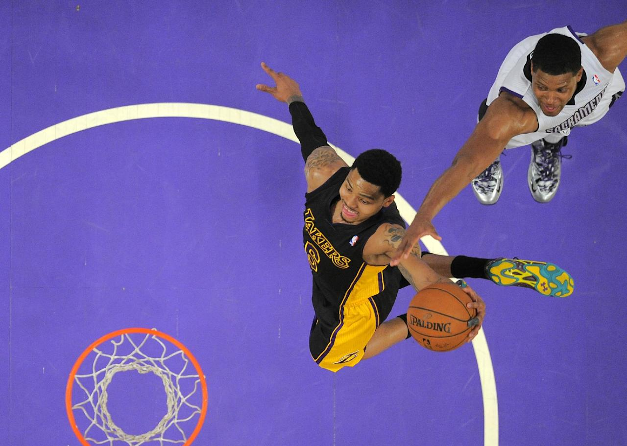 Los Angeles Lakers guard Kent Bazemore, left, goes up for a dunk as Sacramento Kings forward Rudy Gay defends during the first half of an NBA basketball game, Friday, Feb. 28, 2014, in Los Angeles. (AP Photo/Mark J. Terrill)