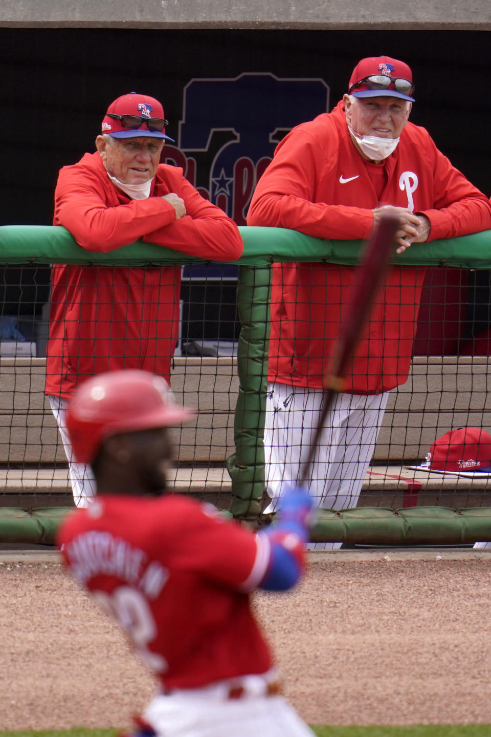 Philadelphia Phillies former managers and spring training coaches Larry Bowa, left rear, and Charlie Manuel, right rear, watch as Andrew McCutchen singles off Detroit Tigers starting pitcher Michael Fulmer during the fifth inning of a spring training exhibition baseball game in Clearwater, Fla., Sunday, March 21, 2021. (AP Photo/Gene J. Puskar)