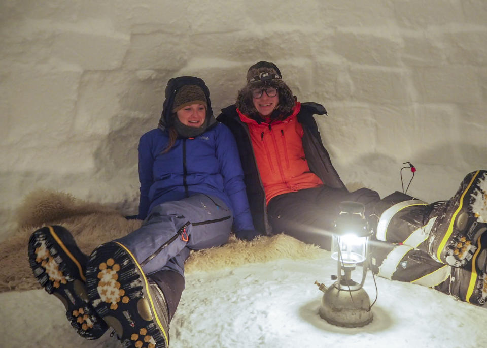 Pictured is field guide Sasha Doyle, left, and meteorological observer Jack Farr, right, sitting in an igloo.