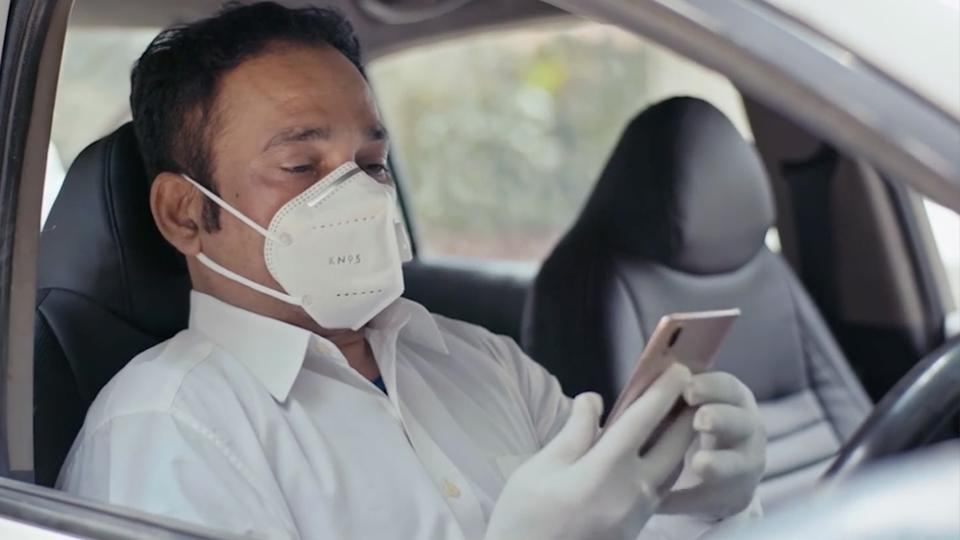 An Ola driver taking a selfie with the new mask selfie app