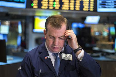 A trader works on the floor of the New York Stock Exchange shortly after the market opening December 16, 2013. REUTERS/Lucas Jackson