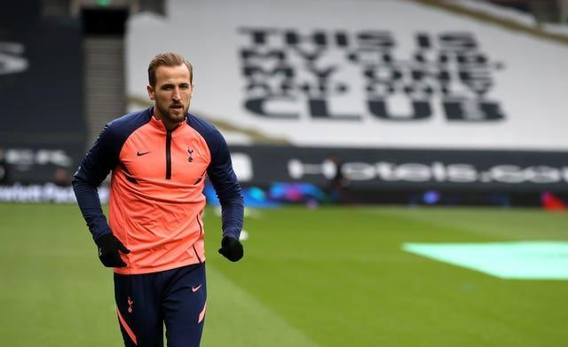 Harry Kane warms up for Tottenham in front of a banner reading