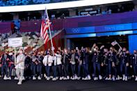 """<p>Business on top, party on the bottom! Team USA, <a href=""""https://people.com/style/caroline-marks-team-usa-ralph-lauren-opening-ceremony-uniforms/"""" rel=""""nofollow noopener"""" target=""""_blank"""" data-ylk=""""slk:dressed by Ralph Lauren"""" class=""""link rapid-noclick-resp"""">dressed by Ralph Lauren</a>, wore dark denim pants, striped shirts and blazers to the opening ceremony. </p>"""