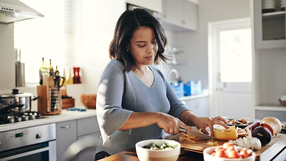 Shot of an attractive young woman cooking at home.