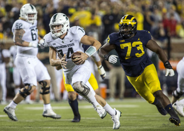 "Michigan State quarterback <a class=""link rapid-noclick-resp"" href=""/ncaaf/players/257176/"" data-ylk=""slk:Brian Lewerke"">Brian Lewerke</a> (14) rushes ahead of Michigan defensive lineman <a class=""link rapid-noclick-resp"" href=""/ncaaf/players/227391/"" data-ylk=""slk:Maurice Hurst"">Maurice Hurst</a> (73) for a touchdown in the first quarter of an NCAA college football game in Ann Arbor, Mich., Saturday, Oct. 7, 2017. (AP Photo/Tony Ding)"